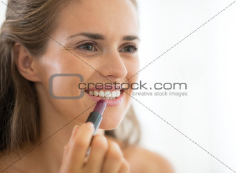 Portrait of happy young woman applying lipstick