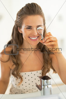 Portrait of happy young woman using eyelash curler in bathroom