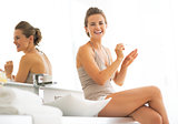 Smiling young woman applying nail polish in bathroom