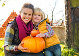 Portrait of happy mother and child holding pumpkin