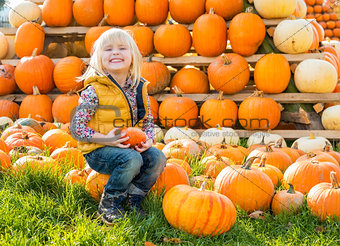 Portrait of happy child sitting on pumpkin
