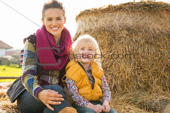 Portrait of happy mother and child sitting on haystack