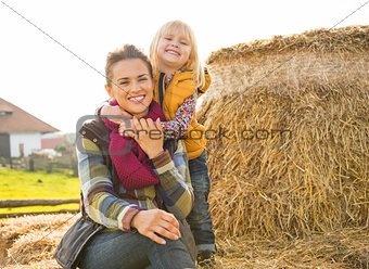 Portrait of smiling mother and child sitting on haystack
