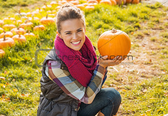 Portrait of happy young woman showing pumpkin