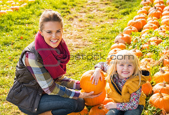 Portrait of happy mother and child among pumpkin
