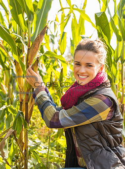 Portrait of happy young woman tearing corn