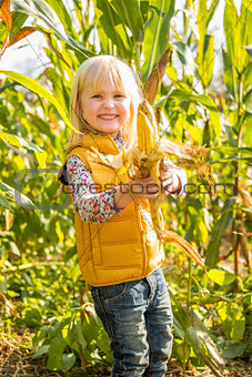 Portrait of smiling child showing corn while in cornfield