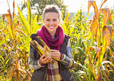 Happy young woman holding corn while standing in cornfield