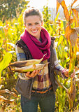 Closeup on smiling young woman giving corns while in cornfield