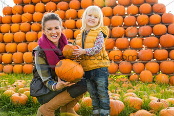 Portrait of happy mother and child choosing pumpkins