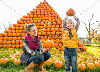 Portrait of happy mother and child pumpkin in front of pumpkin p