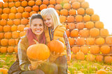 Portrait of happy mother and child holding pumpkins