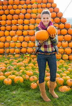 Portrait of happy young woman with pumpkins