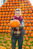 Portrait of smiling young woman holding pumpkin