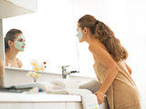 Young woman with facial cosmetic mask looking in mirror in bathr