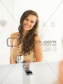 Portrait of happy young woman with wet hair in bathroom