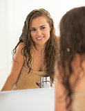 Portrait of happy young woman with wet hair in bathroom looking