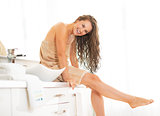Portrait of happy young woman with wet hair sitting in bathroom