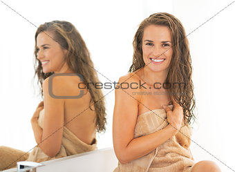 Portrait of happy young woman with wet long hair in bathroom