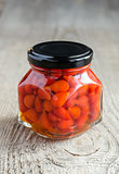 Red peppers drops in glass jar on the wooden background
