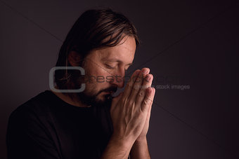 Adult bearded man praying in dark room