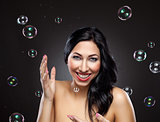 Young and happy woman surrounded by bubbles