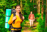 man and woman in the morning in the woods with backpacks