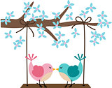Two birds in love on a swing