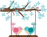 Two birds in love on a swing