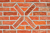 Masonry wall of bricks with a cross as decoration.