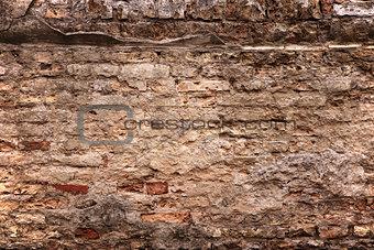 old brick wall with loose bricks and deteriorating mortar