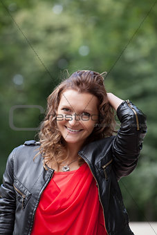 Portrait of young smiling woman in park.