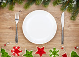Empty plate with silverware, fir tree and christmas decor