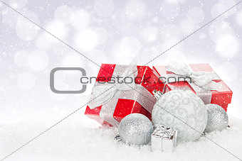 Christmas baubles and red gift boxes over snow bokeh background