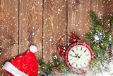 Christmas wooden background with clock, santa hat and snow fir t