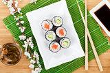 Sushi maki set, green tea and sakura branch