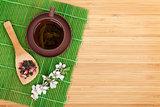 Japanese green tea and sakura branch over mat
