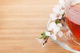 Japanese green tea and sakura branch over mat and bamboo table