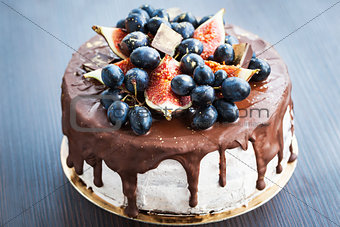 Chocolate cake with icing, decorated with fresh fruit