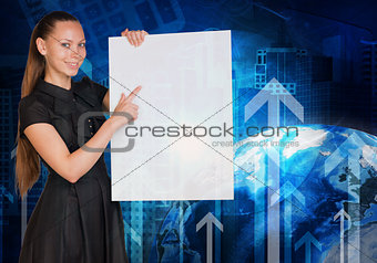Beautiful businesswoman in dress holding empty paper sheet. Earth, arrows and buildings on background