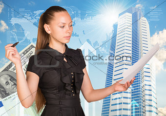 Beautiful businesswoman in dress marker and paper sheets. Building as backdrop