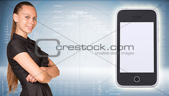 Beautiful businesswoman in dress smiling and looking at camera. Smart phone with empty screen are located near