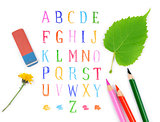 pencils and eraser on the background of the alphabet