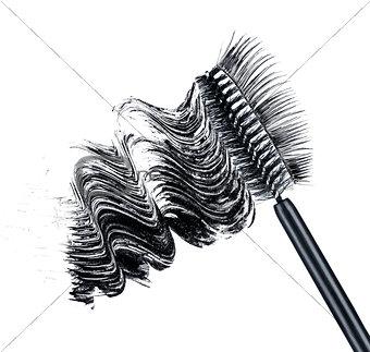 smear of black brush mascara and false eyelashes isolated on whi