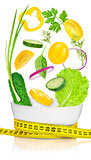 Diet concept. Fresh vegetables falling into the glass bowl isolated over white background