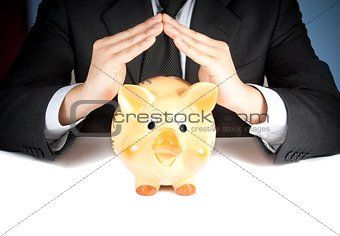 a businessman make with his hand a home behind a piggy bank, concept for business and save money