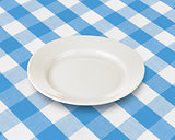 plate or dish over blue checked fabric tablecloth