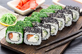 Sushi roll covered with dill and sesame