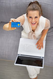Happy young woman with laptop showing credit card