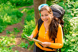 female with map and backpack smiling